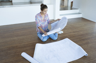 Woman examining blueprints on floor in empty living room - CAIF18570
