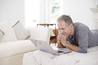 Senior man using laptop in livingroom - CAIF18606
