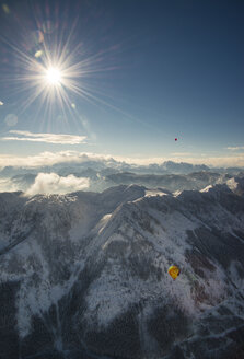 Austria, Salzkammergut, Hot air balloons over alpine landscape in winter - STC00389