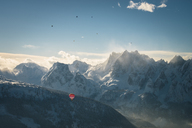 Austria, Salzkammergut, Hot air balloons over alpine landscape with Gosaukamm  in winter - STCF00401