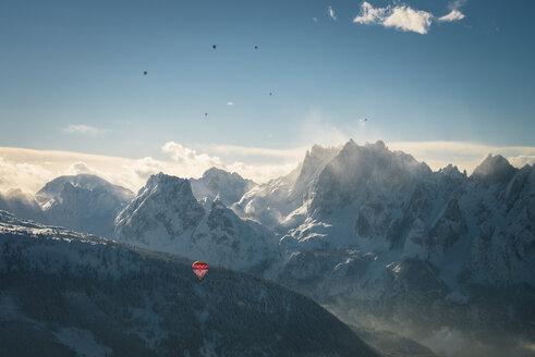 Austria, Salzkammergut, Hot air balloons over alpine landscape with Gosaukamm  in winter - STCF00401