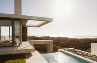 Modern house and swimming pool overlooking ocean - CAIF18792