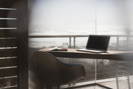Laptop on desk in modern home office overlooking ocean - CAIF18795