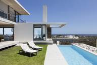 Lounge chairs and lap pool outside modern house - CAIF18804