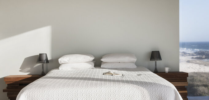 Sun shining on white bed with ocean view - CAIF18810
