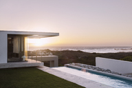 Modern house overlooking ocean at sunset - CAIF18816