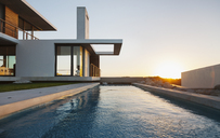 Lap pool outside modern house at sunset - CAIF18819