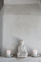 Buddha figurine and candles on ledge - CAIF18849