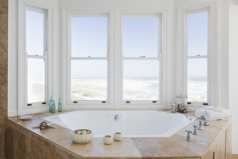 Jacuzzi tub in bathroom overlooking ocean - CAIF18858