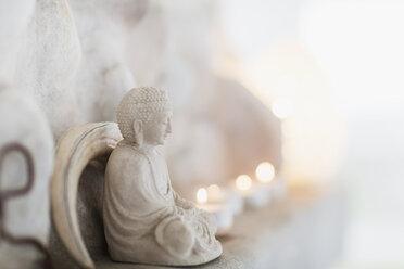 Buddha figurine and candles on ledge - CAIF18864