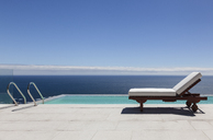 Infinity pool and lounge chair overlooking ocean - CAIF18960