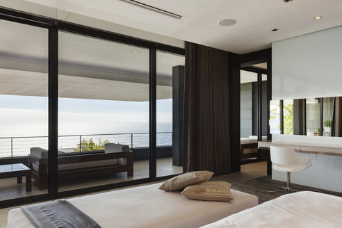 Modern bedroom and balcony overlooking ocean - CAIF18972