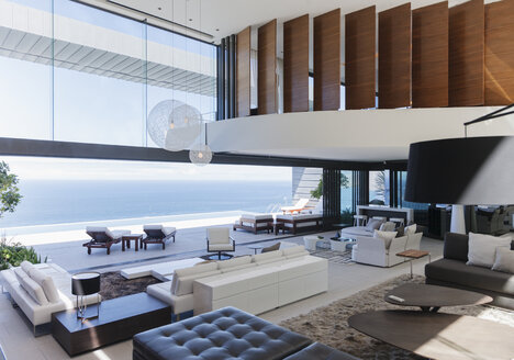 Modern living room overlooking ocean - CAIF18975