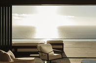 Modern living room overlooking ocean at sunset - CAIF18990