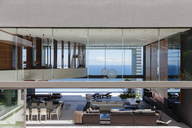 Glass walls of modern house overlooking ocean - CAIF19002