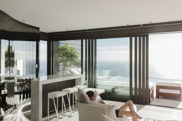 Woman relaxing in modern living room overlooking ocean - CAIF19014