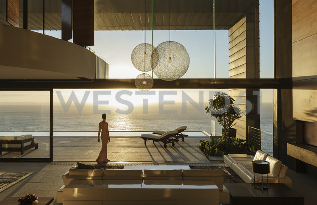 Woman in modern house overlooking ocean - CAIF19023
