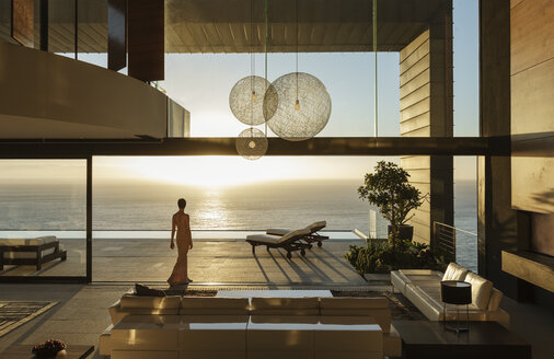 Woman in modern house overlooking ocean - CAIF19023