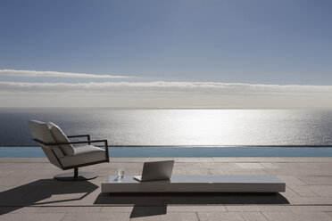 Modern patio and infinity pool overlooking ocean - CAIF19029