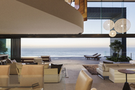 Modern living room overlooking ocean at sunset - CAIF19032