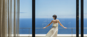 Woman looking at ocean from balcony - CAIF19056