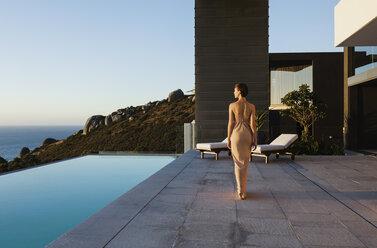Woman in dress walking along infinity pool overlooking ocean - CAIF19062