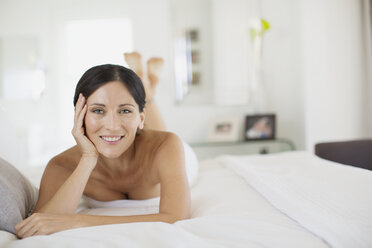 Smiling woman laying on bed - CAIF19320