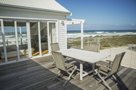 Table and chairs on balcony overlooking beach - CAIF19338
