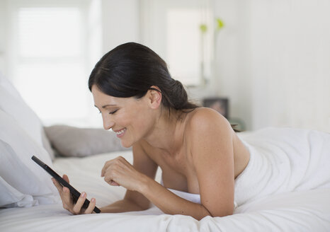 Woman using digital tablet on bed - CAIF19347