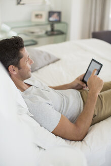 Man using digital tablet on bed - CAIF19365