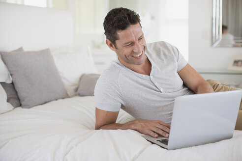 Man using laptop on bed - CAIF19368