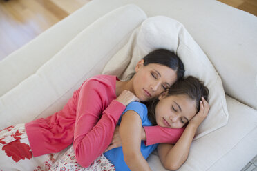 Mother and daughter napping on sofa in living room - CAIF19377