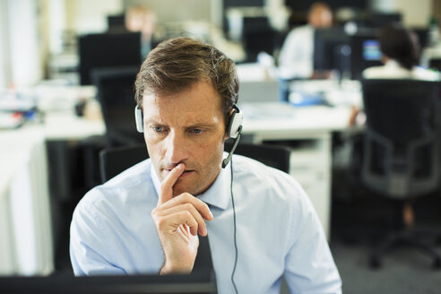 Businessman wearing headset in office - CAIF19395