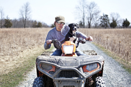 Man with dog riding quadbike on gravel road by field - CAVF09648