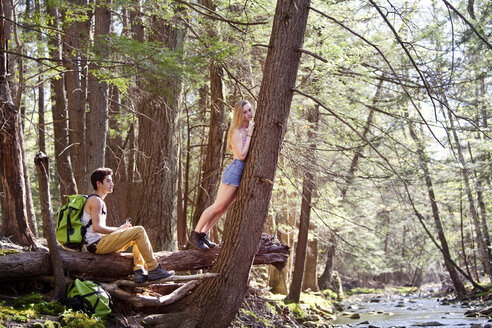 Woman leaning on tree while man sitting on fallen tree trunk - CAVF09711