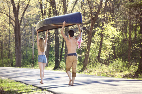 Rear view of couple carrying rowboat while walking on road in forest - CAVF09720