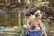 Couple looking in water while sitting on rowboat - CAVF09726
