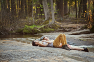 Couple lying on rock at forest - CAVF09741