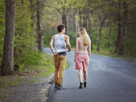 Rear view of couple talking while walking on road - CAVF09744