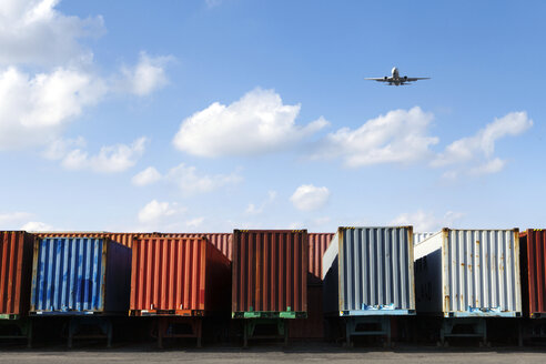 Airplane flying over cargo containers against sky - CAVF09780