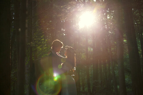Romantic couple standing in forest - CAVF09786
