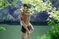 Rear view of man embracing woman while standing at lakeshore - CAVF09828