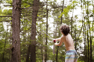 Rear view of boy casting fishing rod while fishing in forest - CAVF09864