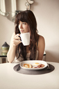 Woman looking away while drinking coffee by table at home - CAVF09957