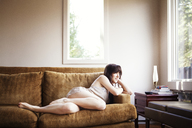 Thoughtful woman looking away while relaxing on sofa at home - CAVF09963