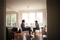 Couple sitting by breakfast table in morning at home - CAVF09972