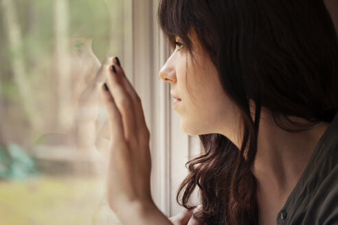 Close-up of woman looking through window at home - CAVF09975