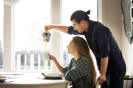 Man pouring coffee for girlfriend at home - CAVF10026