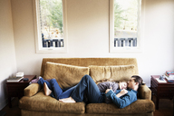 High angle view of couple sleeping on sofa at home - CAVF10044