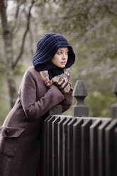 Woman in warm clothing looking away while leaning on fence - CAVF10059